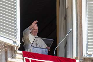 Pope Francis waves as he leads the Angelus from the window of his studio overlooking St. Peter's Square at the Vatican Aug. 16, 2020. The pope appealed for prayers for those who have lost their jobs because of the COVID-19 pandemic.