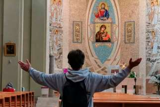 A man raises his arms in prayer at the Church of Santa Maria delle Grazie al Trionfale in Rome March 17, 2020. Many churches in Italy remain open for prayer amid a nationwide lockdown to prevent the spread of the coronavirus.