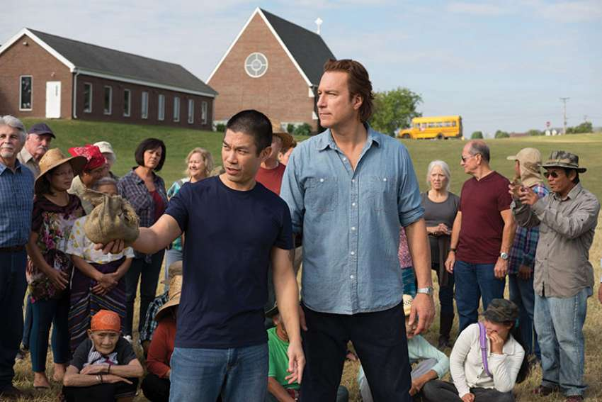Ye Win (Nelson Lee) instructs Rev. Michael Spurlock (John Corbett) where to plant the crops to be grown in the fields at All Saints Church, in the new movie All Saints. At right is Spurlock.