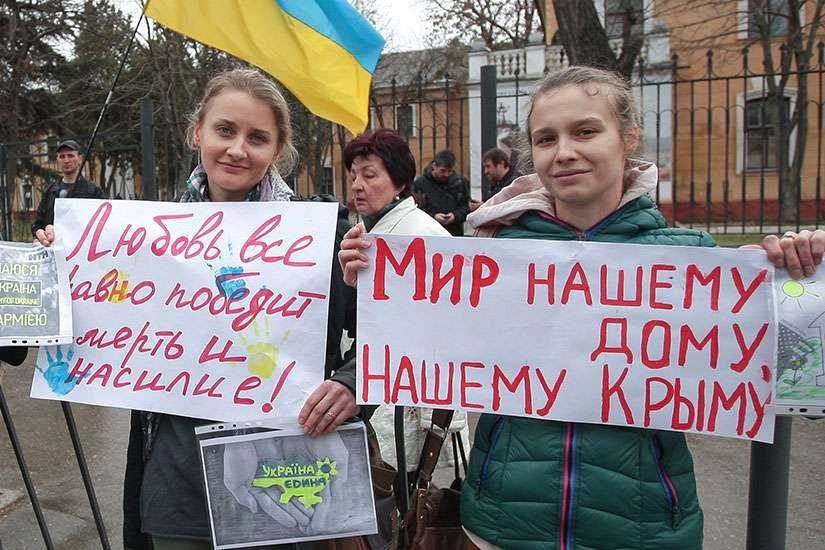Ukrainian women hold peace placards near a military base in Ukraine's Crimea region in this March 4, 2014 file photo.