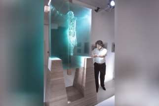 Jed Malitz poses for a photo with his work V2. The glass sculpture depicts the crucifixion and it is produced by light shining through 13 arranged panes of sculpted glass cut using a computer-guided process.