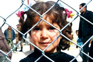 A displaced Syrian girl finds temporary shelter at a school in Damascus, Syria.