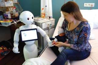 """Pepper,"" a humanoid robot designed to welcome and take care of visitors and patients, holds the hand of a newborn baby next to his mother at AZ Damiaan hospital in Ostend, Belgium. The Vatican's Pontifical Academy for Life has added robotics to its list of specialized areas of study."