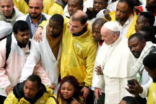 Pope Francis poses with a group of migrants during his general audience Nov. 28 in Paul VI hall at the Vatican.