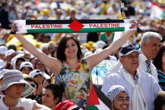 A woman holds a banner with the colors of the Palestinian flag before the start of the canonization Mass for four new saints celebrated by Pope Francis in St. Peter's Square at the Vatican May 17.