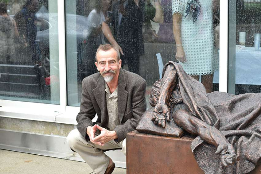 Ed Czuchnicki poses with Timothy Schmalz's When I Was Sick You Visited Me sculpture outside St. Joseph's Hospital in Hamilton.