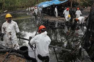 Workers collect oil from a stream below the site of an oil pipeline break in 2016 in Wachapea, Peru. A Peruvian court has upheld the right of Awajun and Wampis indigenous communities to be consulted about oil drilling on their land.
