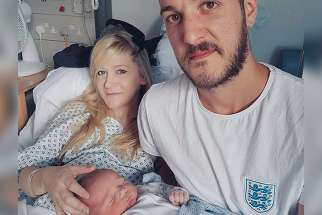 This is an undated handout photo of Chris Gard and Connie Yates with their son, Charlie Gard, provided by the family, at Great Ormond Street Hospital in London.