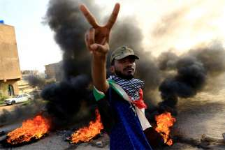 A Sudanese protester gestures during a demonstration in Khartoum July 27, 2019. Bishop Yunan Andali of El Obeid said the country has become too fragile, after months protests in which demonstrators have been pushing for a civilian government.