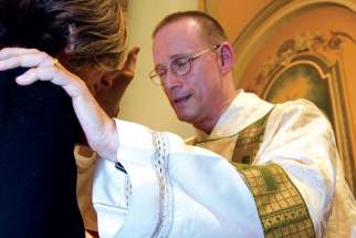 Deacon Stephan Brunck blesses a parishioner at St. Paul's Basilica in Toronto.