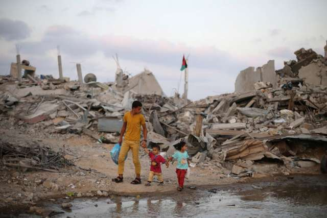 Palestinians in Gaza walk next to the ruins of houses destroyed during the Israeli offensive, on the fifth day of cease-fire in Gaza Aug.18.
