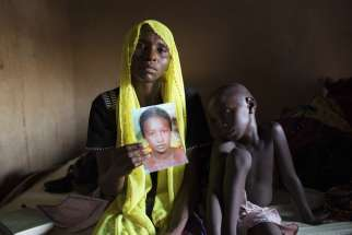 Rachel Daniel, 35, holds up a picture of her abducted daughter, Rose Daniel, 17, as her son Bukar, 7, sits beside her at her home in Maiduguri on May 21, 2014. Rose was abducted along with more than 200 of her classmates on April 14, 2014, by Boko Haram militants from a secondary school in Chibok, Borno state.