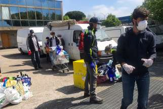 "Volunteers for a local association, ""Cittadini del Mondo,"" work to bring needed assistance to refugees and others living in an occupied building in Rome. The association is concerned 50 occupants recently testing positive for coronavirus may signal more cases to come."