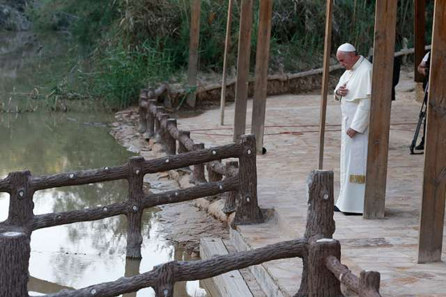 Pope Francis makes the Sign of the Cross after praying as he visits Bethany Beyond the Jordan May 24, believed to be where Jesus was baptized, southwest of Amman.