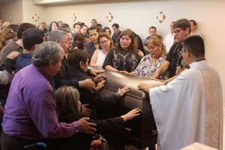 Family and friends of slain journalist Javier Valdez touch his coffin during his May 17 memorial service in Culiacan, Mexico. Valdez was pulled from his car and shot twelve times May 15 in Culiacan, a city currently consumed by drug cartel violence.