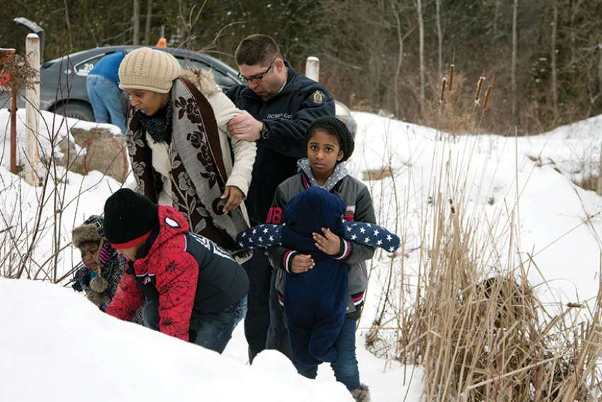 A woman is taken into custody by a Royal Canadian Mounted Police officer after arriving Feb.12 by taxi and walking across the U.S.-Canada border into Quebec last winter. More than 8,000 asylum seekers have crossed from the United States into Canada this year.