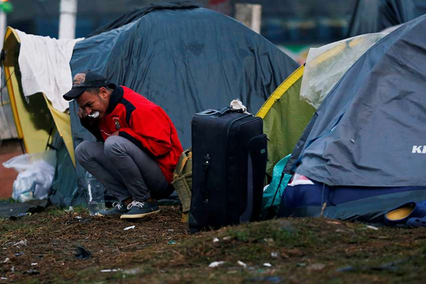 A Venezuelan migrant brushes his teeth outside his tent at a makeshift camp Nov. 26 in Bogota, Colombia. The United Nations estimates there are more than 258 million migrants around the world living outside their country of birth.
