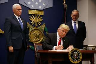 U.S. President Donald Trump signs a revised executive order for a U.S. travel ban March 6 at the Pentagon in Arlington, Va. The executive order temporarily bans refugees from certain majority-Muslim countries, and now excludes Iraq.