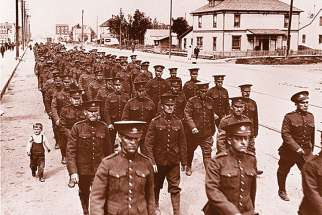 A young child marches alongside Canadian soldiers preparing to be sent off to the First World War. At right is Jesuit Rev. Major William Hingston, who was a chaplain in the Canadian Expeditionary Force during the war.