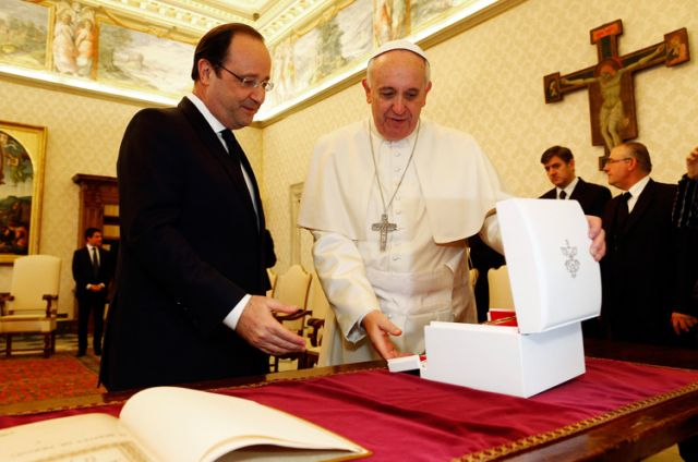 Pope Francis exchanges gifts with French President Francois Hollande during a private audience at the Vatican Jan. 24.
