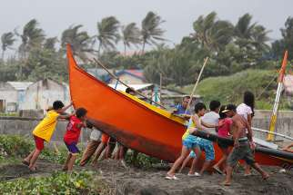 Villagers in Aparri, Philippines, secure a boat Sept. 14 in preparation for super Typhoon Mangkhut. The storm threatens more than 4 million people in the north of the country.