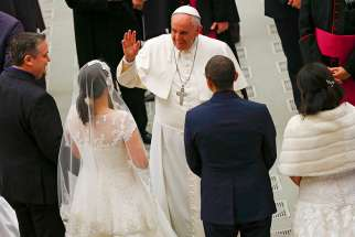 Pope Francis gestures to newlywed couples during his weekly audience in Paul VI hall at the Vatican 2015.