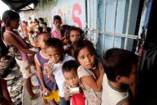 Children living in a squatters' area wait for a free meal consisting of rice, chicken and vegetables that is given out daily near Manila, Philippines.
