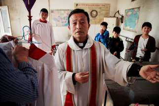 A priest gestures while vesting for Palm Sunday Mass March 25 at a Catholic church in Youtong, in China's Hebei province.