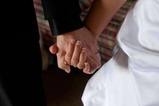A groom and bride hold hands on their wedding day.