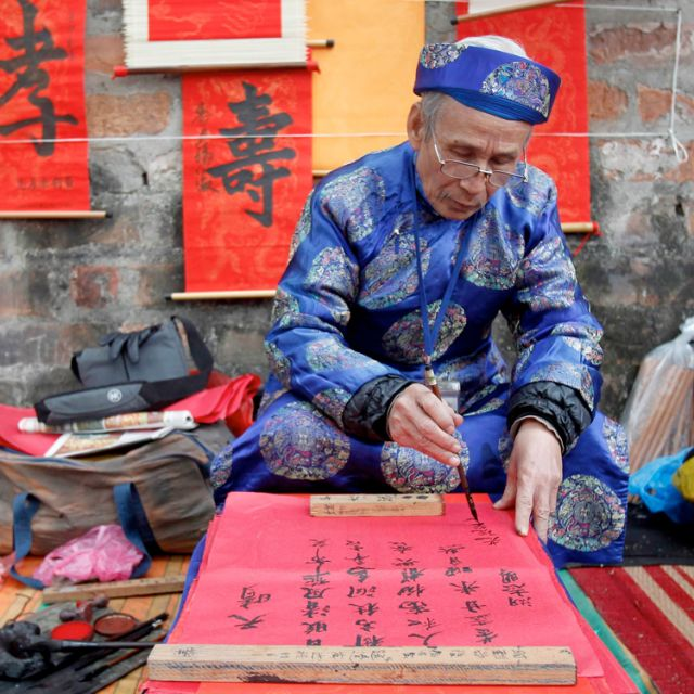 A calligrapher paints while waiting for customers on a street in Hanoi, Vietnam, Jan. 13. Calligraphy paintings are used for decoration during Tet, the Vietnamese lunar new year, which begins Jan. 23.