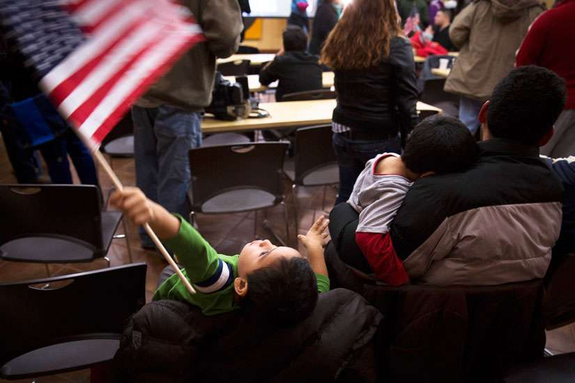 A boy waves the American flag Nov. 20, 2014 at CASA de Maryland's Multicultural Center in Hyattsville, Md., after hearing President Barack Obama's national address on immigration. A U.S. federal judge ordered the Obama administration to release the immigrant mothers and children locked in detention centres by Oct. 23, 2015.