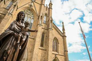 A statue of Mary holding the baby Jesus stands outside St. Michael's Cathedral Basilica in Toronto.