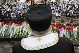 A clergyman stands near photos of people killed in Ukrainian protests in 2014, during a Feb. 20 commemorating ceremony in Kiev's Independence Square.