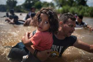 A man, part of a caravan of migrants from Central America to the United States, carries a girl Oct. 29 through the Suchiate River into Mexico from Guatemala.