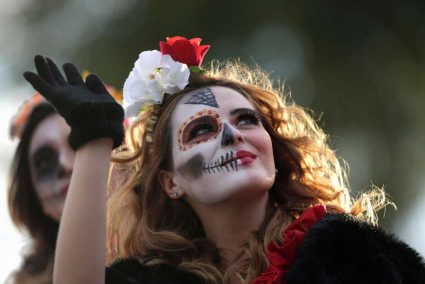 "A woman dressed as ""Catrina"" takes part in a parade Oct. 27, 2019, ahead of Day of the Dead in Monterrey, Mexico. Day of the Dead is a Mexican custom traditionally observed Nov. 1 and 2 to remember family and friends who have died."