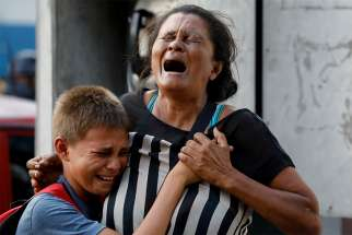 A woman and boy mourn outside a police station jail March 28 in Valencia, Venezuela. At least 68 people, mostly prisoners, were killed in a fire at the jail.