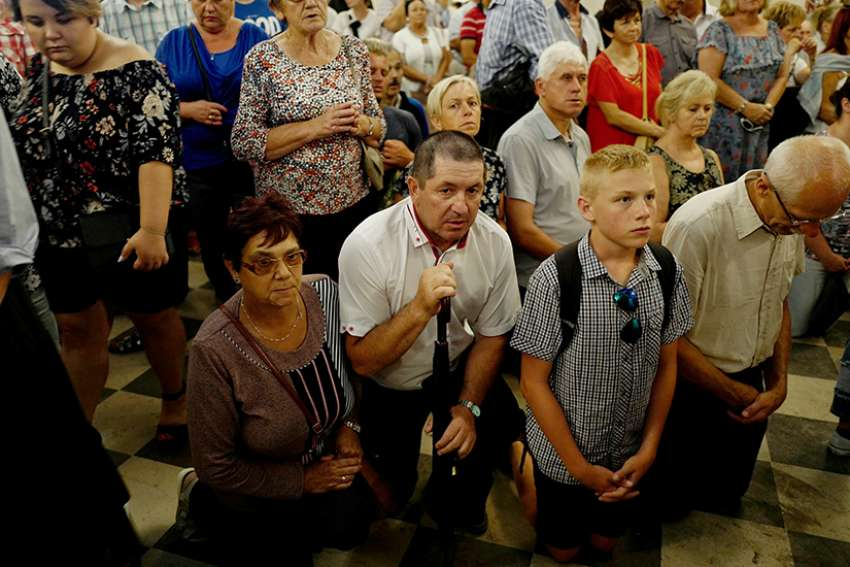 Worshippers pray during celebrations on the feast of the Assumption, Aug. 15, 2018, at Jasna Gora Monastery in Czestochowa, Poland. The Vatican secretary of state praised the Polish church's traditional closeness to Rome as key to its survival under hostile regimes, in a speech marking the centenary of the nation's conference of bishops and diplomatic ties with the Vatican.