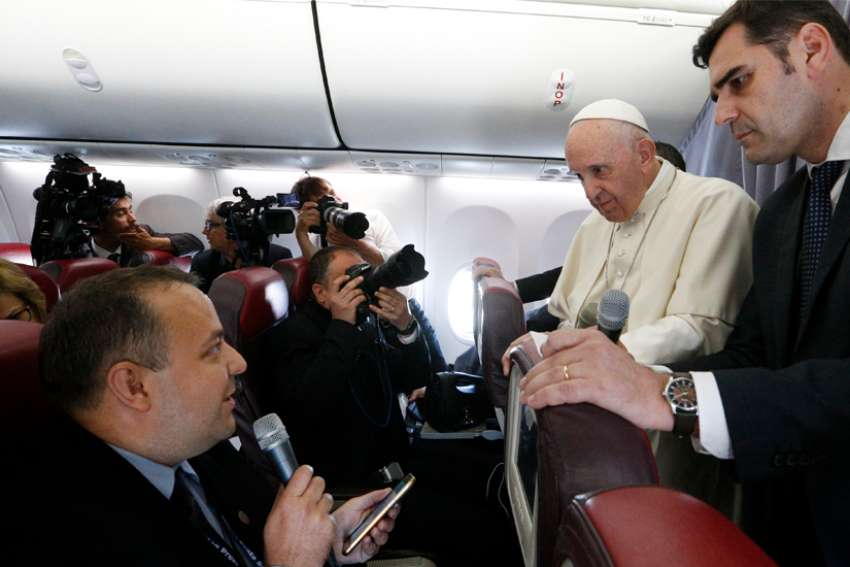 Pope Francis listens to a question from Romanian journalist Cristian Micaci aboard his flight from Sibiu, Romania, to Rome June 2, 2019.