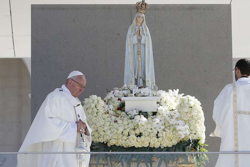 Pope Francis uses incense as he venerates a statue of Our Lady of Fatima during the canonization Mass of Sts. Francisco and Jacinta Marto, two of the three Fatima seers, at the Shrine of Our Lady of Fatima in Portugal, May 13. The Mass marked the 100th anniversary of the Fatima Marian apparitions, which began on May 13, 1917.