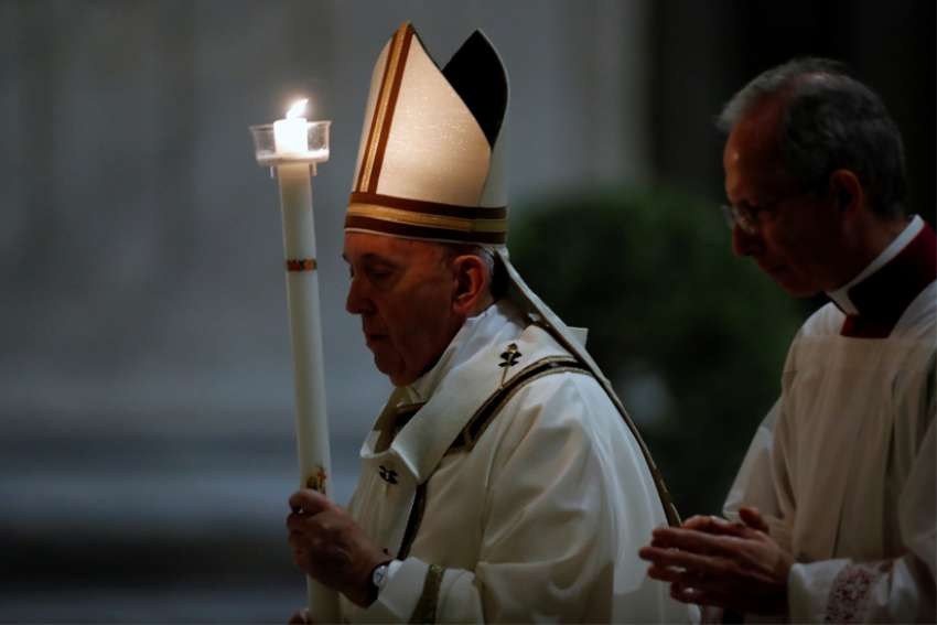 Pope Francis carries a candle at the start of the Easter vigil in St. Peter's Basilica at the Vatican April 11, 2020. The Mass was celebrated without the presence of the public due to the coronavirus crisis.