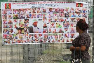 A woman in Bayelsa, Nigeria, reads a Nigerian army poster picturing wanted Boko Haram suspects May 19, 2016.