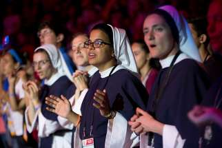 Women religious pray as the Blessed Sacrament is processed through the Knights of Columbus Mercy Centre during World Youth Day events July 27.