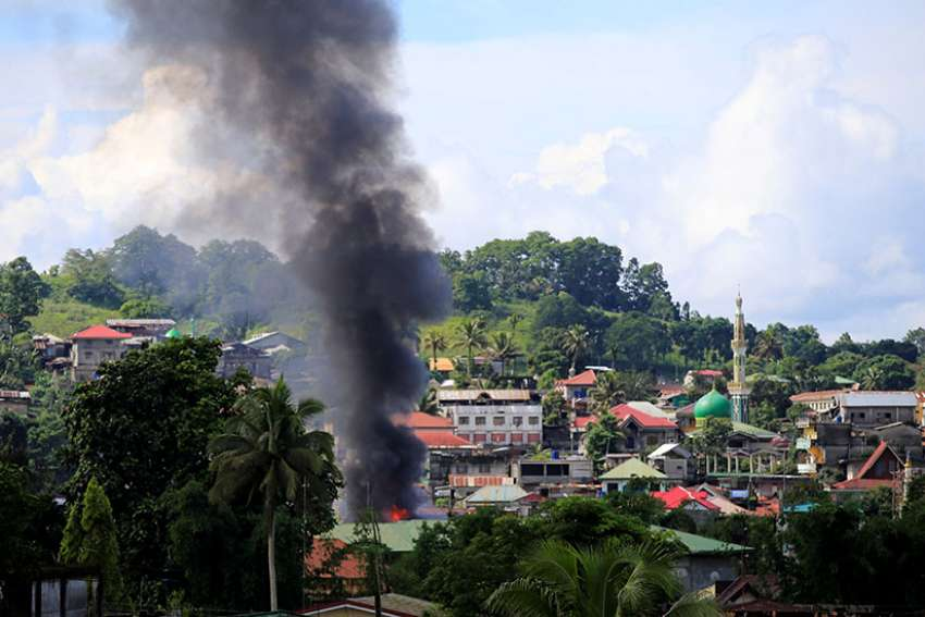 Smoke billows from a burning building as government troops continued their assault on Islamic militants June 1 in Marawi, Philippines.