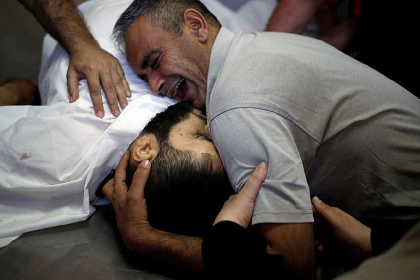 The brother of Palestinian Shaher al-Madhoon, who was killed during a protest at the Israel-Gaza border, reacts over his body May 14 at a hospital morgue in Gaza.