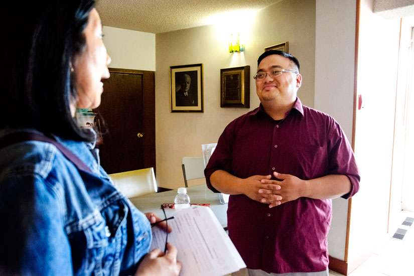 Chico Nuguid, the full-time youth minister at Precious Blood Parish in Toronto, is questioned by a parent parisher interested in sending her child to the summer camp he will be running at the younger part of the congregation.