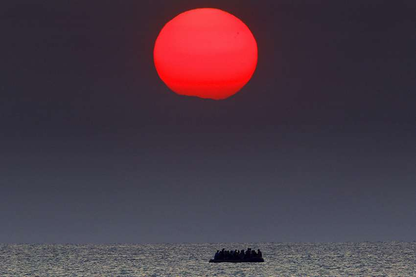 A red sun is seen over a dinghy overcrowded with Syrian refugees drifting in the Aegean sea between Turkey and Greece after its motor broke down off the Greek island of Kos, August 11, 2015.
