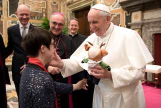 Pope receives a stuffed animal from a participant in the Special Olympics during a meeting Feb. 16 at the Vatican. The athletes and organizers were at the Vatican to promote the Special Olympics World Winter Games, which will be held in Austria March 14-25.