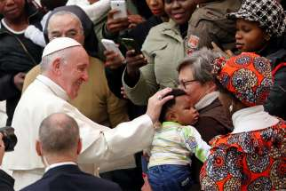 Pope Francis greets a child as he arrives to lead his general audience in Paul VI hall at the Vatican Dec. 19.