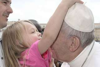Little Estella steals Pope Francis' zucchetto as he gives her a kiss during his weekly general audience March 22.