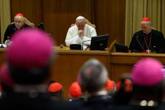 Pope Francis attends the morning session on the final day of the extraordinary Synod of Bishops on the family at the Vatican Oct. 18. At left is Cardinal Lorenzo Baldisseri, general secretary of the Synod of Bishops, and at right Cardinal Peter Erdo of E sztergom-Budapest, Hungary, relator for the synod.